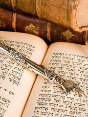 Silver Torah pointer lying on a jewish prayer book